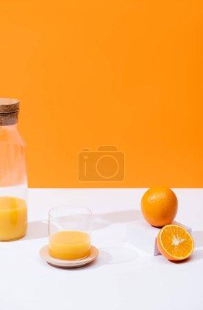 fresh orange juice in glass and bottle near oranges on white surface isolated on orange