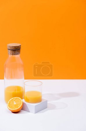 Photo for Fresh orange juice in glass and bottle near cut fruit on white surface isolated on orange - Royalty Free Image