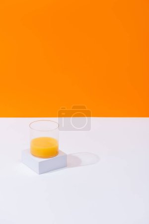 fresh orange juice in glass on white surface isolated on orange