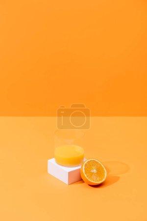 Photo for Fresh orange juice in glass near half of orange and white cube isolated on orange - Royalty Free Image