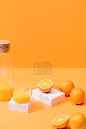 Photo pour Jus d'orange frais en verre et bouteille près des oranges mûres et des cubes blancs isolés sur orange - image libre de droit