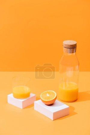 Photo pour Jus d'orange frais en verre et en bouteille près de cubes d'orange et de blanc coupés isolés sur orange - image libre de droit