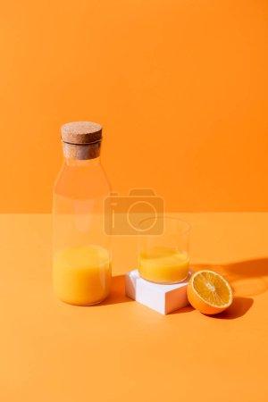 Photo for Fresh orange juice in glass and bottle near half of orange and white cube isolated on orange - Royalty Free Image
