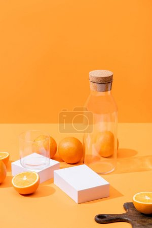 Photo pour Jus d'orange frais en verre et bouteille près d'oranges mûres, planche à découper en bois isolée sur orange - image libre de droit