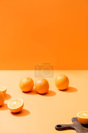Photo pour Oranges fraîches mûres et planche à découper en bois isolée sur orange - image libre de droit