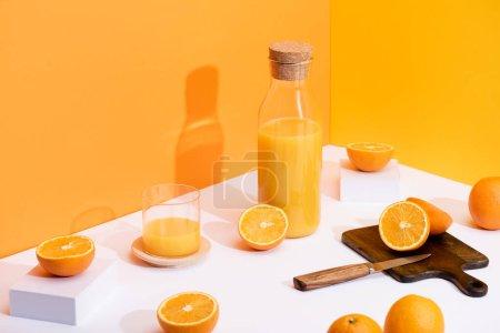 Photo pour Jus d'orange frais en verre et bouteille près d'oranges mûres, planche à découper en bois avec couteau sur fond blanc sur fond orange - image libre de droit