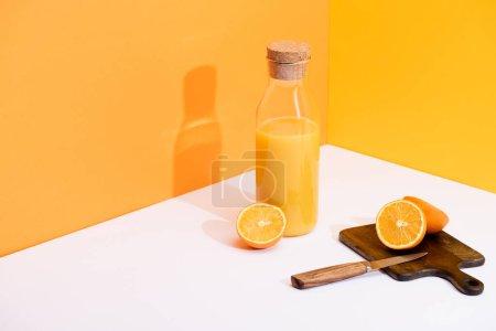 Photo pour Jus d'orange frais en bouteille de verre près d'oranges mûres, planche à découper en bois avec couteau sur fond blanc sur fond orange - image libre de droit