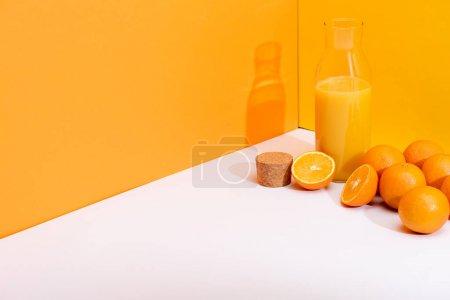 Photo for Fresh orange juice in glass bottle near ripe oranges and cork on white surface on orange background - Royalty Free Image