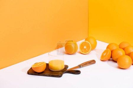 fresh orange juice in glass on wooden cutting board with knife near ripe oranges on white surface on orange background