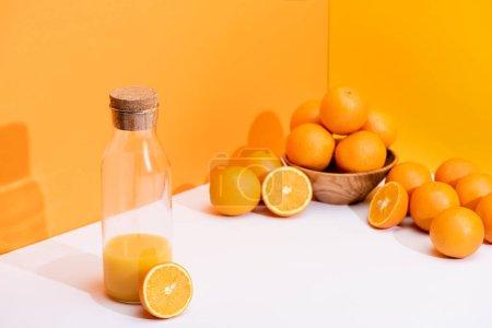 fresh orange juice in glass bottle near ripe oranges in bowl on white surface on orange background