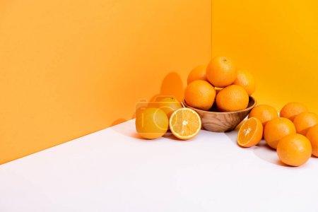 fresh ripe oranges in bowl on white surface on orange background