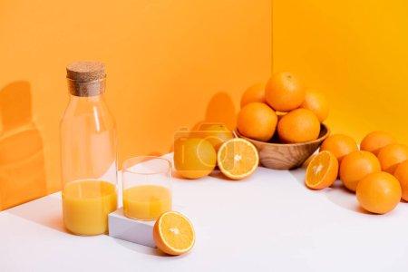 Photo pour Jus d'orange frais en verre et bouteille près des oranges mûres dans un bol sur fond blanc sur fond orange - image libre de droit