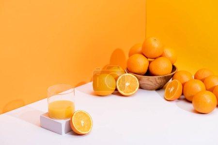 Photo for Fresh orange juice in glass near ripe oranges in bowl on white surface on orange background - Royalty Free Image