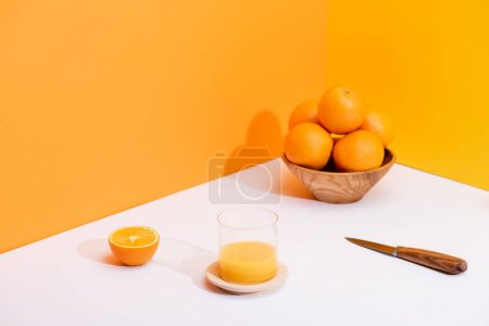 fresh orange juice in glass near ripe oranges in bowl and knife on white surface on orange background