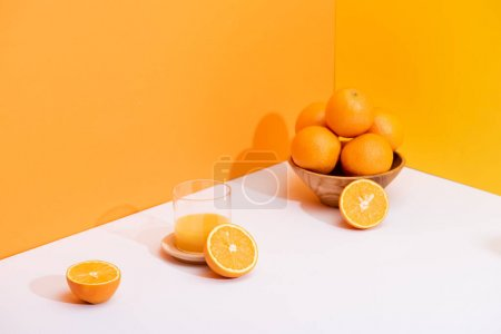 Photo for Fresh orange juice in glass near ripe oranges in bowl on white surface on orange background - Royalty Free Image