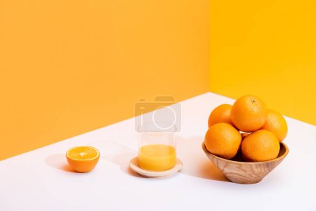 fresh orange juice in glass near ripe oranges in bowl on white surface on orange background