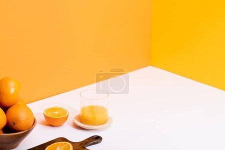 Photo pour Jus d'orange frais en verre près des oranges mûres dans un bol et planche à découper en bois sur fond blanc sur fond orange - image libre de droit