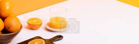 Photo pour Jus d'orange frais en verre près d'oranges mûres dans un bol et planche à découper en bois sur une surface blanche sur fond orange, plan panoramique - image libre de droit