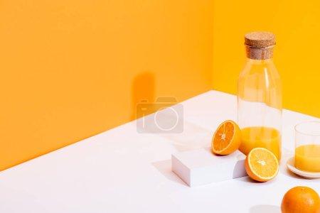 Photo pour Jus d'orange frais en verre et bouteille près des oranges mûres sur fond blanc sur fond orange - image libre de droit