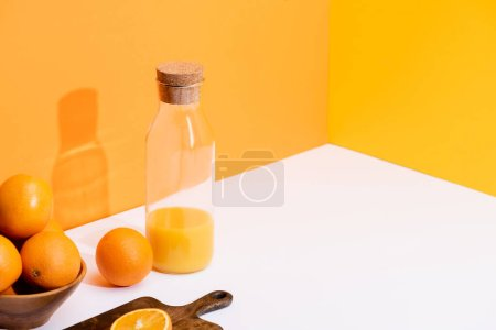 Photo pour Jus d'orange frais dans une bouteille de verre près d'oranges mûres dans un bol et planche à découper sur une surface blanche sur fond orange - image libre de droit