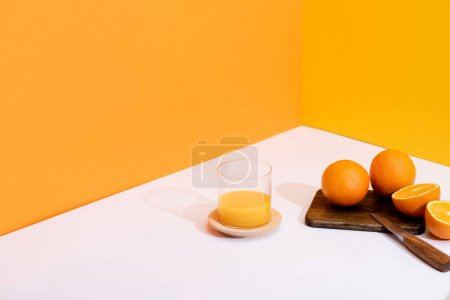 Photo pour Jus d'orange frais en verre près des oranges mûres sur planche à découper avec couteau sur fond blanc sur fond orange - image libre de droit