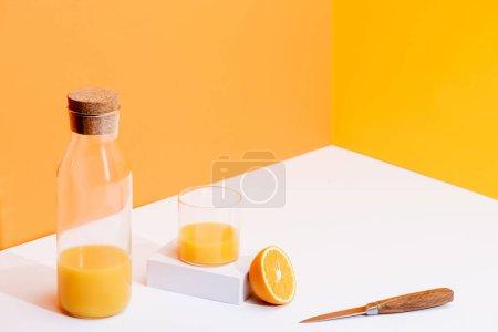 Photo pour Jus d'orange frais en verre et bouteille près de l'orange mûre et couteau sur fond blanc sur fond orange - image libre de droit