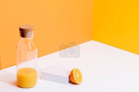 Foto de Jugo de naranja fresco en botella de vidrio cerca de naranja maduro en la superficie blanca sobre fondo naranja. - Imagen libre de derechos