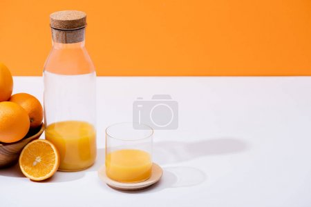 Photo for Fresh orange juice in glass and bottle near oranges in wooden bowl on white surface isolated on orange - Royalty Free Image