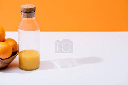 Photo pour Jus d'orange frais en bouteille de verre près des oranges dans un bol en bois sur surface blanche isolé sur orange - image libre de droit