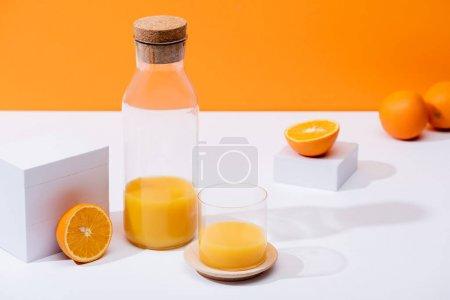 Photo pour Jus d'orange frais en verre et bouteille près d'oranges mûres sur surface blanche isolée sur orange - image libre de droit