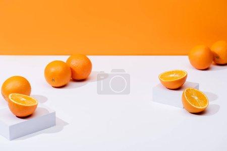 fresh ripe oranges on white surface isolated on orange