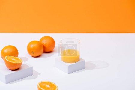 Photo for Fresh orange juice in glass near ripe oranges on white surface isolated on orange - Royalty Free Image