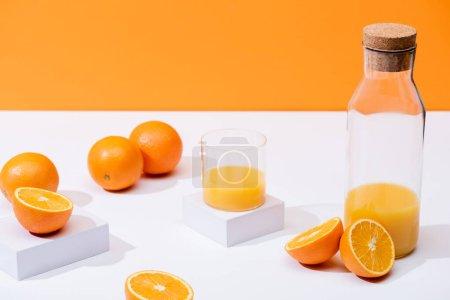 jus d'orange frais en verre et bouteille près d'oranges mûres sur surface blanche isolée sur orange
