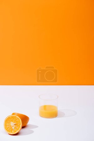 Photo for Fresh orange juice in glass near ripe oranges on white surface isolated on orange - Royalty Free Image
