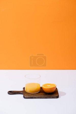 fresh orange juice in glass near cut fruit on wooden cutting board on white surface isolated on orange