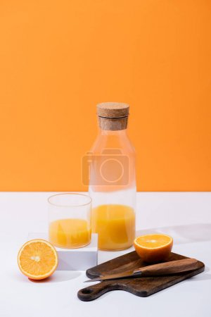 fresh orange juice in glass and bottle near cut fruit on wooden cutting board with knife on white surface isolated on orange