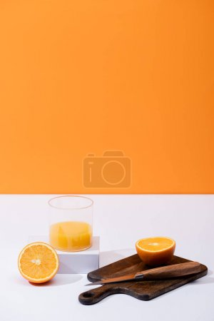 fresh orange juice in glass near cut fruit on wooden cutting board with knife on white surface isolated on orange
