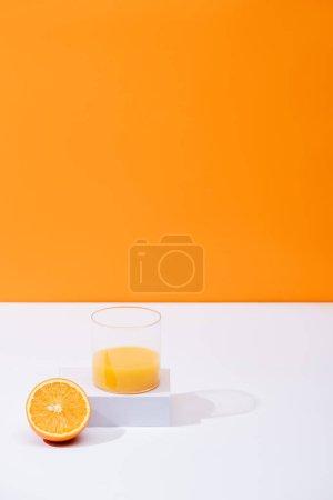 fresh orange juice in glass near cut fruit on white surface isolated on orange