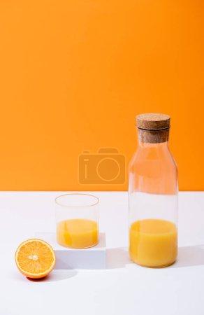 Photo pour Jus d'orange frais en verre et bouteille avec liège près des fruits coupés sur surface blanche isolé sur orange - image libre de droit