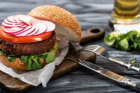Photo for Selective focus of tasty vegan burger with radish and tomato served on cutting board with cutlery on wooden table - Royalty Free Image
