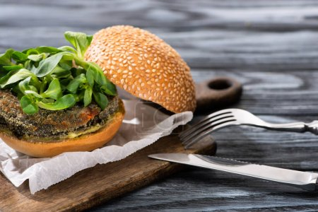 Photo for Tasty vegan burger with microgreens served on cutting board with cutlery on wooden table - Royalty Free Image