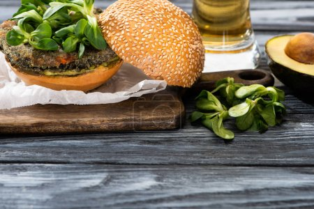 Photo for Tasty vegan burger with microgreens served on cutting board near avocado and beer on wooden table - Royalty Free Image