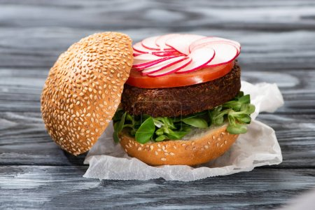 Photo for Tasty vegan burger with radish served on wooden table - Royalty Free Image