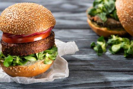 Photo pour Foyer sélectif de hamburgers végétaliens savoureux avec microgreens et légumes servis sur une table en bois - image libre de droit
