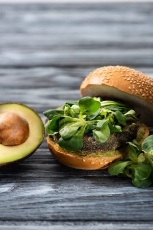 Photo for Tasty vegan burger with microgreens served on wooden table with avocado half - Royalty Free Image