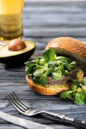 selektiver Schwerpunkt leckerer veganer Burger mit Mikrogemüse auf Holztisch mit Avocadohälfte, Besteck und Bier