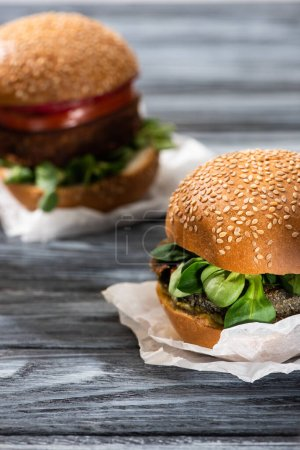 Photo for Selective focus of tasty vegan burgers with microgreens served on wooden table - Royalty Free Image