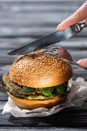 Photo for Cropped view of woman cutting tasty vegan burger with fork and knife - Royalty Free Image