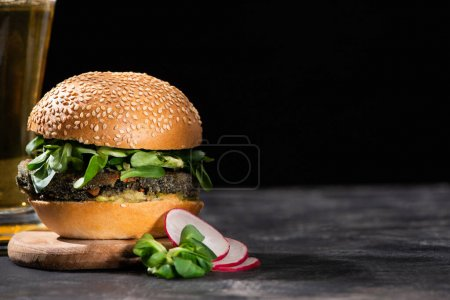 Photo for Selective focus of tasty vegan burger with microgreens served with beer and radish on textured surface isolated on black - Royalty Free Image