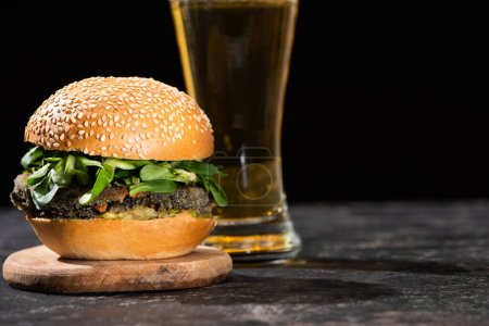 Photo for Selective focus of tasty vegan burger with microgreens served with beer on textured surface isolated on black - Royalty Free Image
